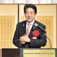 Prime Minister Shinzo Abe speaks at the Sheraton Miyako Hotel Tokyo during an event Monday marking the 50th anniversary of the normalization of diplomatic ties between Japan and South Korea. | YOSHIAKI MIURA