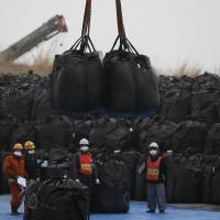 Workers move large black plastic bags containing irradiated soil, leaves and debris from the ongoing decontamination operation at a temporary storage site in the town of Tomioka, Fukushima Prefecture, in February. | REUTERS
