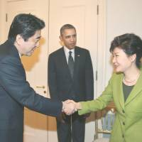 Prime Minister Shinzo Abe and South Korean President Park Geun-hye shake hands as U.S. President Barack Obama looks on before their March 2014 trilateral meeting in the Hague. | YONHAP / KYODO