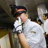 Takashi Arai, assistant stationmaster at Tokyo's Shinjuku Station on the Marunouchi Line operated by Tokyo Metro Co., speaks over a wireless microphone on the platform during morning rush hour last month. | BLOOMBERG