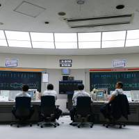 Tokyo Metro Co. employees observe traffic indication panels while working at the company's Integrated Control Center in the capital in May. | BLOOMBERG