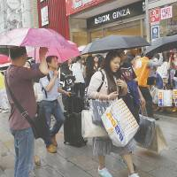 Chinese tourists with shopping bags wait for a sightseeing bus in front of a discount electronics store in Tokyo's Ginza district on June 17. | AP