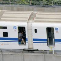 A passenger sits by the door of a shinkansen train that came to a halt on Tuesday in Odawara, Kanagawa Prefecture, with reports of smoke aboard. Initial reports suggested two passengers were dead. | KYODO