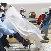 Ambulance staff remove an injured passenger on a stretcher from the Nozomi 225 bullet train at Odawara Station in Kanagawa Prefecture, which the train motored to after making an emergency stop Tuesday. The roughly 800 people aboard left the train at the station. | REUTERS