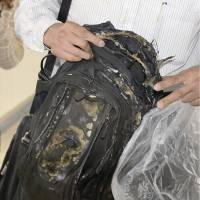 A passenger aboard Tuesday's Nozomi 225 bullet train on the Tokaido Shinkansen Line shows his charred backpack after he and other passengers were moved to nearby Odawara Station in Kanagawa Prefecture. | KYODO