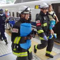 Firefighters carry a child off the platform of Odawara Station, in Kanagawa Prefecture, after the Tokaido shinkansen made an  emergency stop on Tuesday. | KYODO