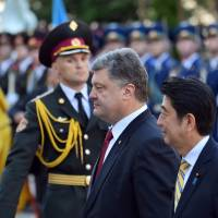 Ukrainian President Petro Poroshenko and Prime Minister Shinzo Abe walk in front of an honor guard during a welcoming ceremony in Kiev on Saturday. | AFP-JIJI