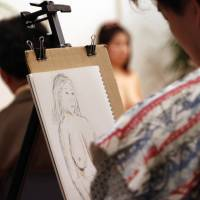 People, including middle-aged men, sketch a nude model at a studio in Tokyo. | AFP-JIJI