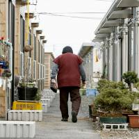 An elderly resident walks among cluttered temporary housing units in Koriyama, Fukushima Prefecture, in March. | KYODO