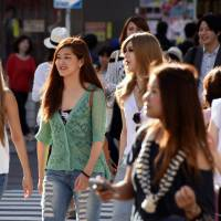 Three 19-year old pedestrians (left) cross a crowded intersection in Tokyo's Shibuya Ward on Thursday, the same day the Lower House passed a bill to lower the voting age to 18. | SATOKO KAWASAKI