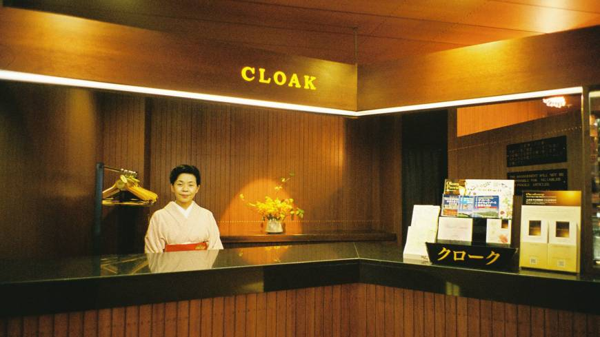 A woman attends a desk for the cloak room in May. | MIRI MATSUFUJI