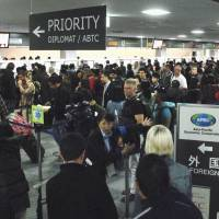 Guiding lines: A group of travelers arrives at the immigration section of Narita International Airport. While the lines look long, Japan's reputation for work conditions may be turning people off of coming to the country. | KYODO