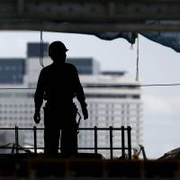 Building Japan: A construction worker surveys a demolished building at a site in Tokyo last week. Many older construction workers, however, are at the mercy of low-paying jobs with no pensions. | REUTERS
