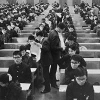 Just write what we tell you: Students sit an exam at Waseda University in Tokyo in 1966. With much of the emphasis still on standardized tests, how much has really changed in Japanese education in the past 50 years? | KYODO