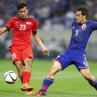 Singapore's Zulfahmi Arifin  (left) and Japan's Shinji Okazaki vie for the ball during Tuesday's 2018 World Cup qualifier at Saitama Stadium. The match ended in a 0-0 draw. | AP