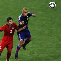 Japan's Keisuke Honda (right) and Singapore's Shaiful Esah were unable to end the scoreless draw during Tuesday's World Cup qualifier. | AP