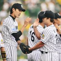 The Tigers celebrate after a win over the Swallows on Sunday. | KYODO
