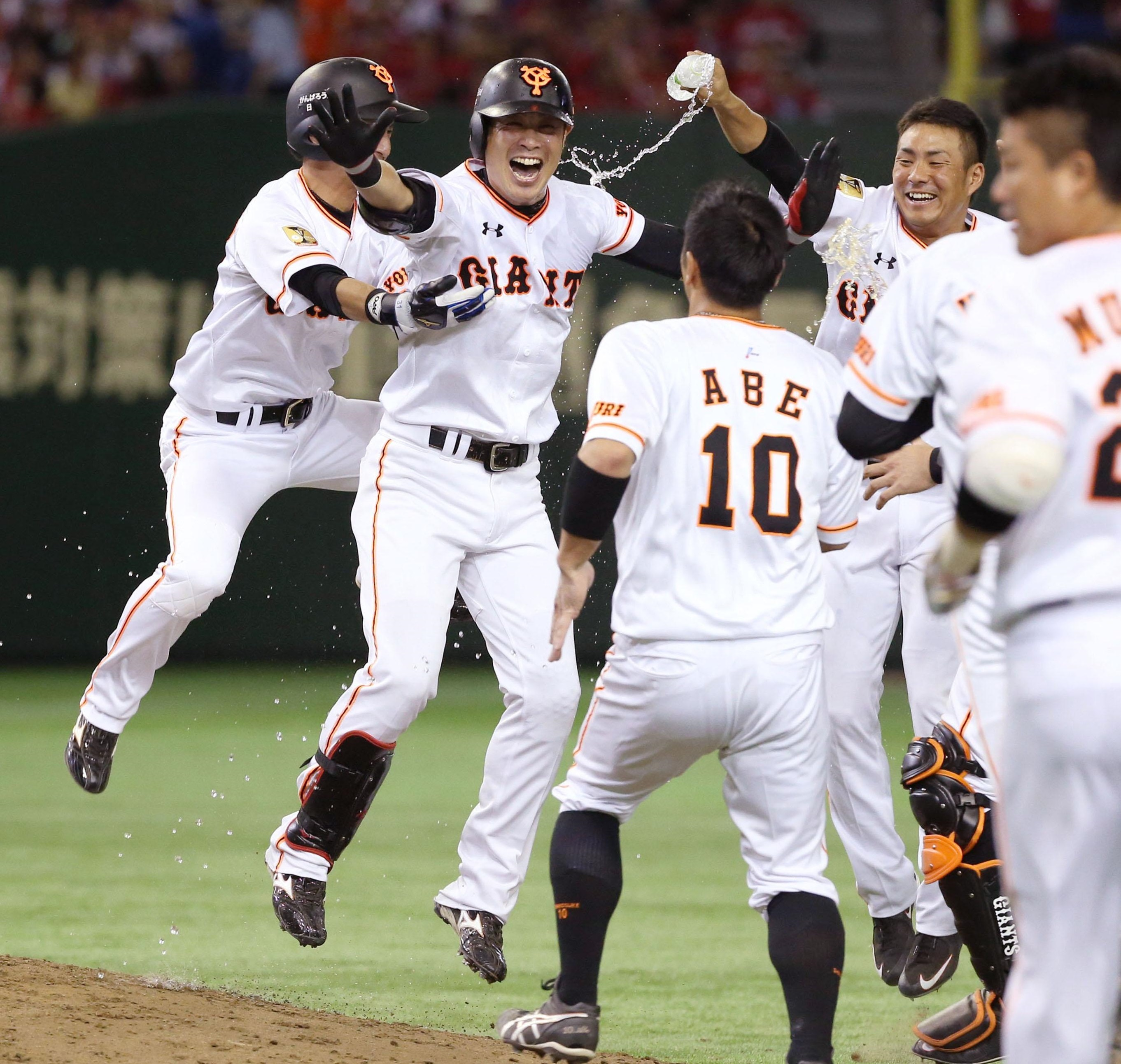 Yoshiyuki Kamei (second from left) and his Giants teammates celebrate their walk-off victory over the Carp on Tuesday night at Tokyo Dome. Kamei hit the game-winning sacrifice fly in Yomiuri's 2-1 triumph over Hiroshima. | KYODO