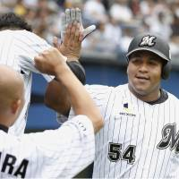 Chiba Lotte's Alfredo Despaigne is congratulated by teammates after hitting a home run in the third inning on Saturday.  | KYODO