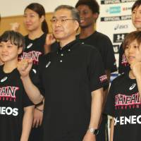 Japan women's national basketball team head coach Tomohide Utsumi (center) and his players pose for a photo before opening their training camp at the National Training Center on Wednesday. | KAZ NAGATSUKA