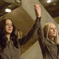 Revolutionary muse: Jennifer Lawrence's Katniss (left) becomes an important tool for Julianne Moore's character, President Alma Coin (right), in 'The Hunger Games: Mockingjay — Part 1.' | TM & © 2015 LIONS GATE FILMS INC. ALL RIGHTS RESERVED.