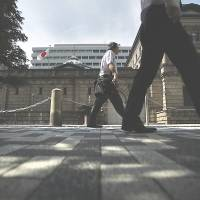 Pedestrians pass the Bank of Japan headquarters in Tokyo in May. The BOJ refrained from increasing monetary stimulus even as it trimmed its outlook for inflation. | BLOOMBERG