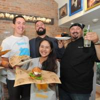 New York-based Bareburger Group CEO Euripides Pelekanos (second from right) and CBO John Simeonidis Jr. (left) poses with Natsumi Otsuka, manager of Bareburger in Japan (front), on Wednesday in its outlet in Tokyo. | YOSHIAKI MIURA