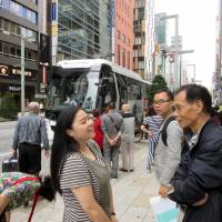 Chinese tourists chat in the Ginza shopping district in central Tokyo. The recent surge in Chinese visitors to Japan is sparking a boom in demand for tour buses. | KYODO