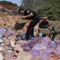 Police pour gasoline on confiscated smuggled meat before setting it on fire during a massive destruction campaign in Hekou county, Yunnan province, China, July 8. | REUTERS