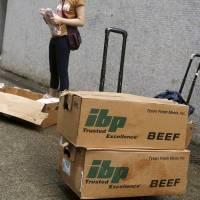 A woman holds unpacked frozen beef ribs from the United States along a back alley at an industrial area in Hong Kong, before the meat is hand-carried and smuggled across the border into mainland China, on Monday. | REUTERS