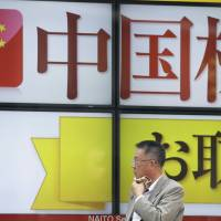 A pedestrian wipes his neck as he stands in front of an electronic board displaying an advertisement for Chinese stocks outside a securities firm in Tokyo on Tuesday. | BLOOMBERG