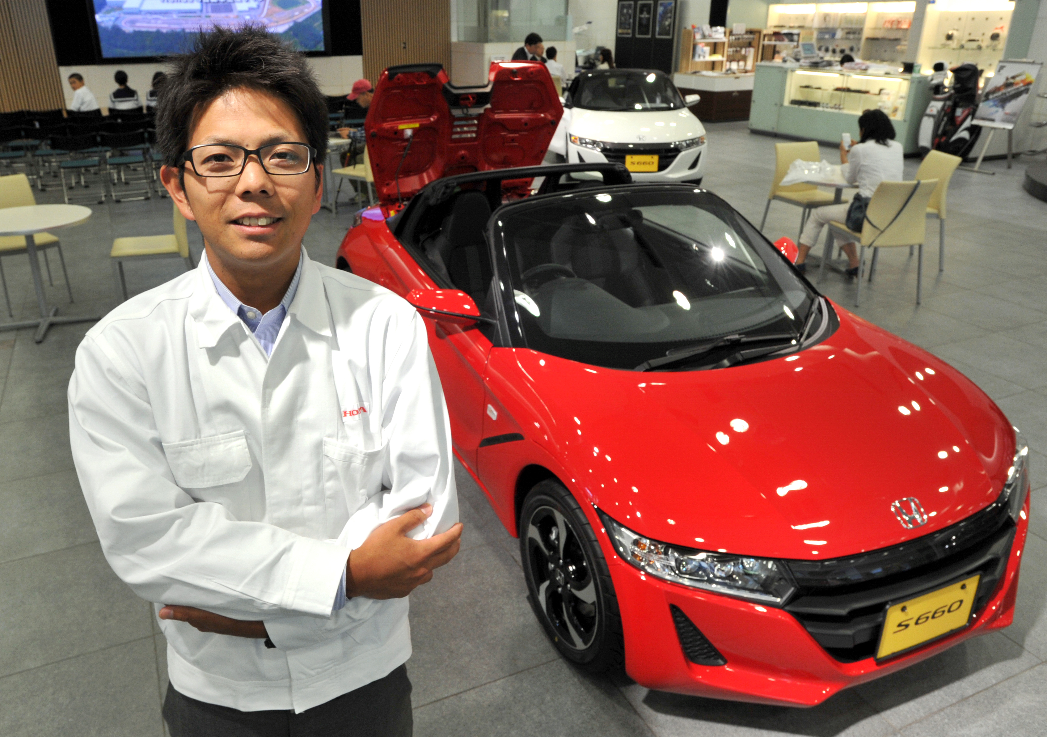 Ryo Mukumoto, the youngest ever manager to oversee the development of a new Honda Motor Co. car, poses with the S660 sports car, at Honda headquarters in Tokyo in May.   YOSHIAKI MIURA