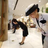 Store attendants welcome the first customers of the day as doors open at the Mitsukoshi department store, operated by Isetan Mitsukoshi Holdings Ltd., in the Nihonbashi district of Tokyo on June 29. | BLOOMBERG
