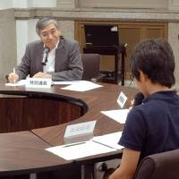 Bank of Japan Gov. Haruhiko Kuroda listens to a junior high school boy during a summer seminar for kids hosted by the central bank Tuesday in Tokyo.   KYODO