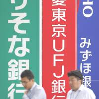 Pedestrians walk past signage for three major banks in Tokyo. Japan's mega-banks are planning to launch bonds that offer great return, at greater risk. | BLOOMBERG