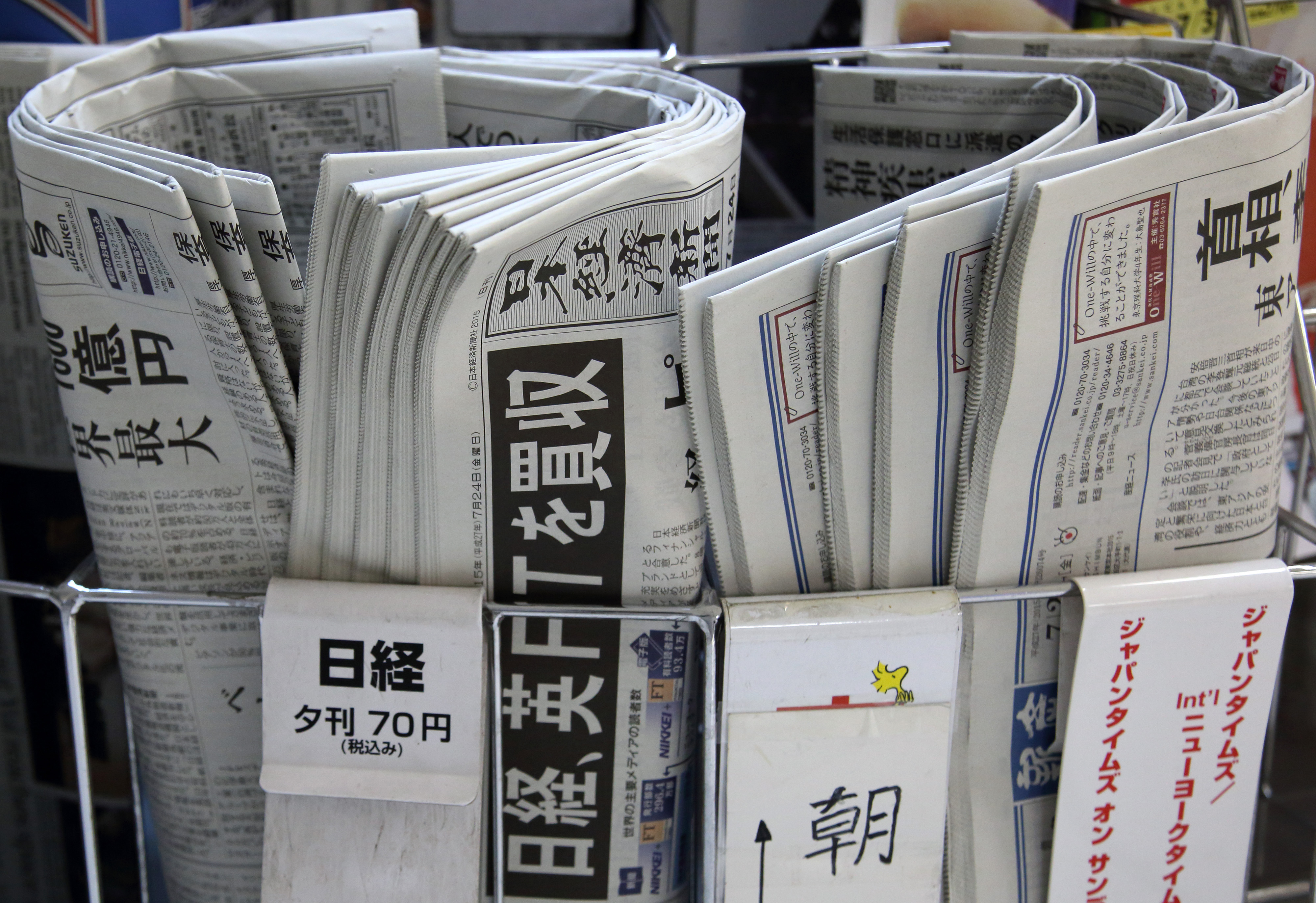 Newspapers, including the Nikkei (center), are displayed for sale in Tokyo on Friday. The headline set in black says 'Nikkei buys British FT.' | BLOOMBERG