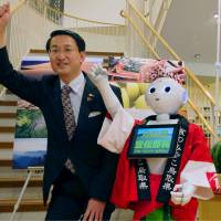 Tottori Gov. Shinji Hirai shows SoftBank's humanoid robot Pepper, assigned as Tottori's tourism promotion chief, at the prefecture's satellite shop in Tokyo Wednesday. | KYODO