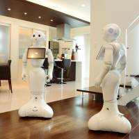 Pepper robots run through their paces at a Yamada Wood House Co. showroom in Osaka on Friday. | KYODO