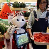 SoftBank's humanoid robot Pepper helps promote watermelons from Tottori Prefecture, at a shop offering local produce Wednesday in Tokyo. Pepper can be hired for sales promotions for ¥1,500 an hour from SoftBank's robotics subsidiary. | AFP-JIJI