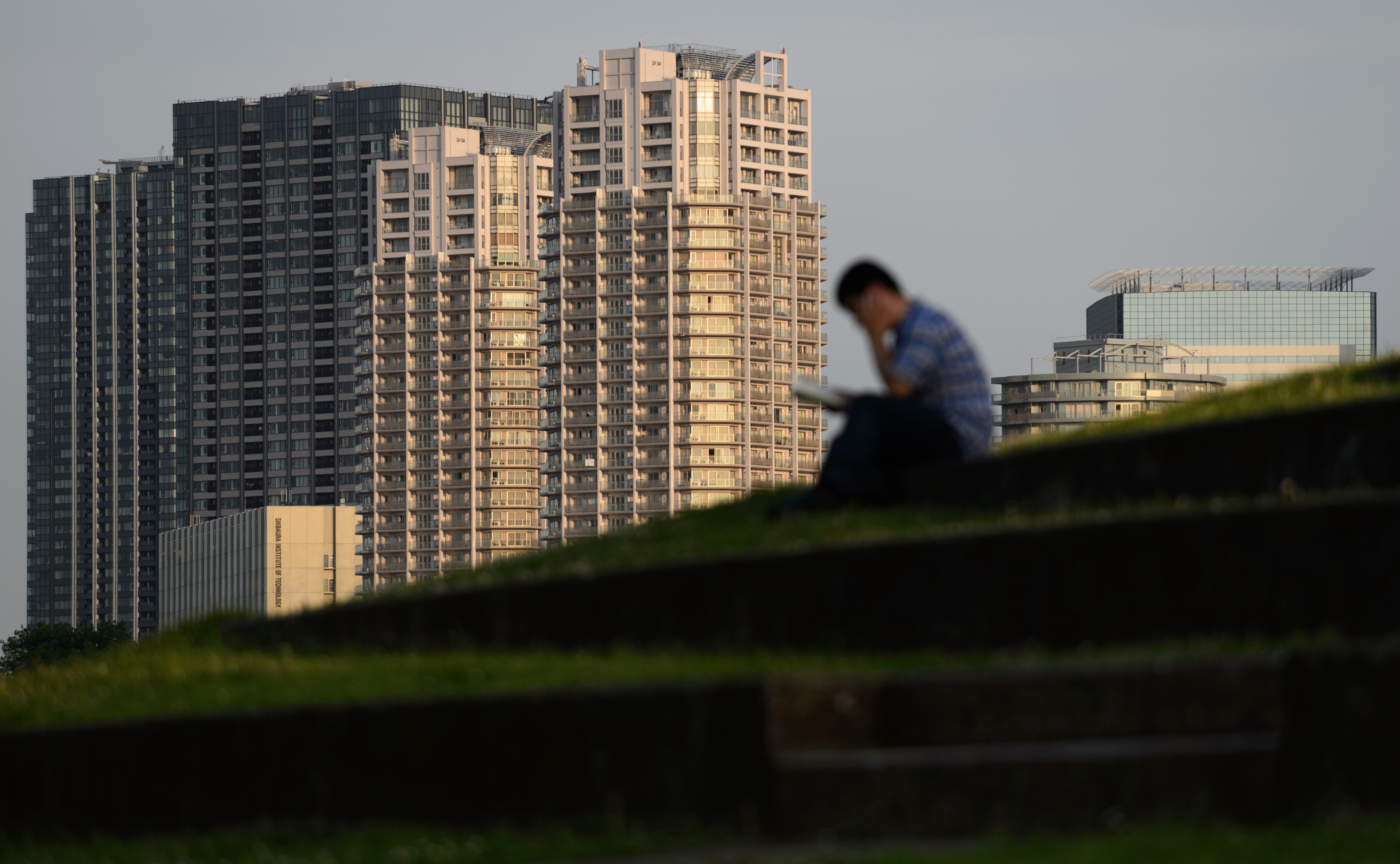 A man sits in front of residential buildings in Tokyo in June. Property prices in Tokyo are inching up as Chinese buyers flock there.   BLOOMBERG