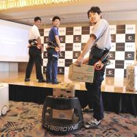 A model wearing a HAL exoskeletal robot suit uses its power to load a box of drinks onto a new transport robot during a demonstration Thursday at Haneda airport. | YOSHIAKI MIURA