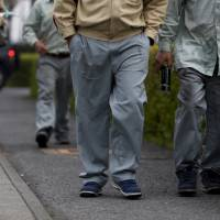 Foreign workers of NHK Spring Co., commonly known as Nippatsu, walk on a street near a Nippatsu factory in Ota, Gunma Prefecture, on April 24. | REUTERS