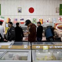 Shoppers look at items at a supermarket selling Brazilian groceries in Ota, Gunma Prefecture, in April. | REUTERS