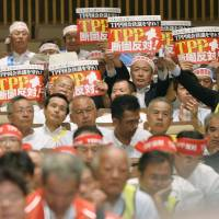 Japanese farmers hold up placards as they take part in a rally opposing the Trans-Pacific Partnership initiative in Tokyo on Monday. The event was held one day before trade ministers from the 12 Pacific Rim nations resumed talks on the deal in Hawaii. | KYODO