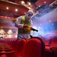 South Korean workers wearing protective gear fumigate a theater at the Sejong Culture Center in Seoul last month during an outbreak of Middle East respiratory syndrome (MERS) that triggered widespread panic and stymied growth in Asia's fourth-largest economy. | AFP-JIJI