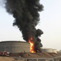 Firefighters work to extinguish a fire following rocket attacks by Shiite rebels known as Houthis at storage tanks of an oil refinery in the port city of Aden, Tuesday. Yemeni forces battling the Shiite rebels in the country's south said they took control on Tuesday of the airport in the strategic port city of Aden, driving the rebels there into the part of the city jutting out into the sea.   AP