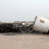 The debris of a plane is seen on the tarmac at Aden's international airport on Tuesday.   AFP-JIJI
