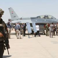 A member of the Iraqi SWAT team stands as security forces and others gather next to one of four new U.S.-made F-16 fighter jets during the delivery ceremony at Balad air base, 75 km (45 miles) north of Baghdad, Iraq, Monday.  Iraqi forces Tuesday carried out a large offensive against Islamic State forces in Anbar province. | AP