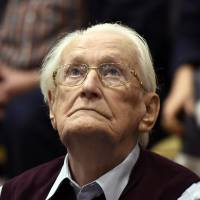 Former SS Sgt. Oskar Groening, 94, looks up as he listens to the verdict of his trial Wednesday at a court in Lueneburg, northern Germany. Groening, who served at the Auschwitz death camp, was convicted on 300,000 counts of accessory to murder and given a four-year sentence. | AP