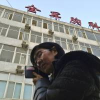 In this March 2014 image, Wang Yu, a lawyer representing human rights activist Cao Shunli, can be seen talking on the phone in front of a Beijing hospital where Cao was being treated in intensive care. Wang had been barred from visiting Cao. | REUTERS